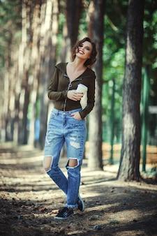 Schönes modell, das freizeitkleidung trägt, die pappbecher in ihrer hand hält