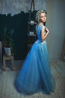 Schönes modell, das hellblaues kleid trägt, posiert in einem studio