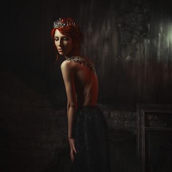 Schönes modell, das kreatives körperkunstkleid trägt, posiert in einem dunklen studio