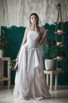 Schönes modell, das weißes spitzenkleid trägt, posiert in einem innenstudio