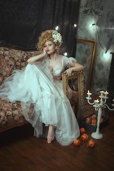 Schönes modell, das weißes spitzenkleid trägt, posiert