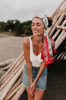 Schönes modell im jeansrock und im tragen eines schals auf dem kopf, der am strand nahe ozean mit wunderbarem lächeln aufwirft