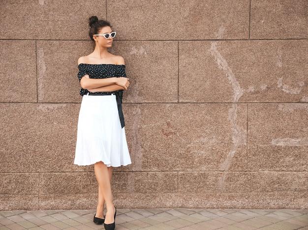 Schönes modell kleidete in der eleganten sommerkleidung an sexy sorgloses mädchen, das in der straße nahe wand aufwirft trendy moderne geschäftsfrau in der sonnenbrille, die spaß hat