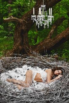 Schönes modell mädchen mit perfektem körper in spitzen dessous schläft in einem riesigen nest im grünen mystischen wald