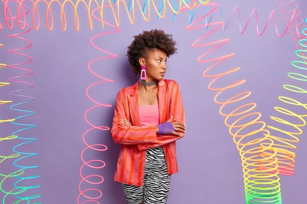 Schönes modell mit ernstem ausdruck, hat stilvolles lockiges haar, steht in selbstbewusster haltung, schaut weg, gekleidet in modisches outfit