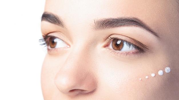 Schönes modell mit kosmetischen tropfen der creme auf ihrem gesicht