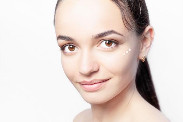 Schönes modell mit kosmetischen tropfen der feuchtigkeitscreme auf ihrem gesicht auf weißer hintergrundnahaufnahme