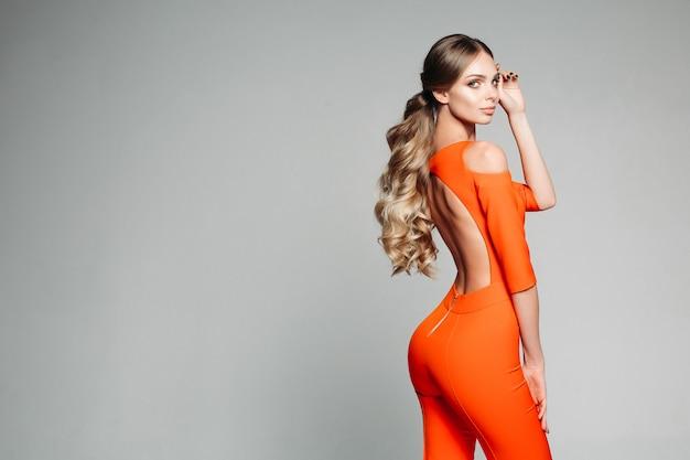 Schönes modell mit langen gewellten haaren im schwanz, die einen orangefarbenen overall mit offenem rücken tragen