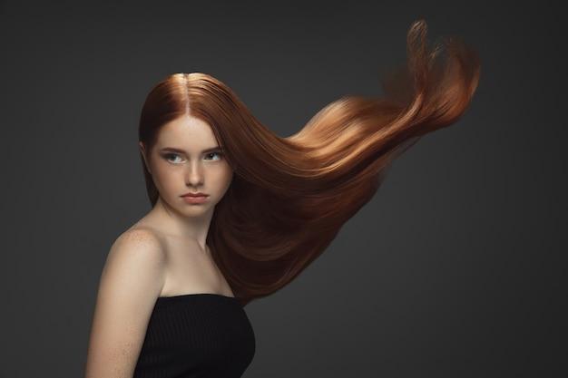 Schönes modell mit langen glatten, fliegenden roten haaren einzeln auf dunklem studiohintergrund.