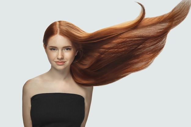 Schönes modell mit langen glatten, fliegenden roten haaren isoliert auf weißem studiohintergrund.