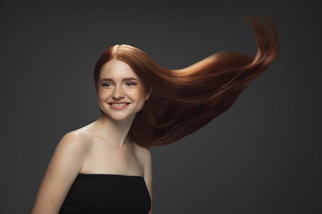 Schönes modell mit langen glatten, fliegenden roten haaren lokalisiert auf dunkelheit