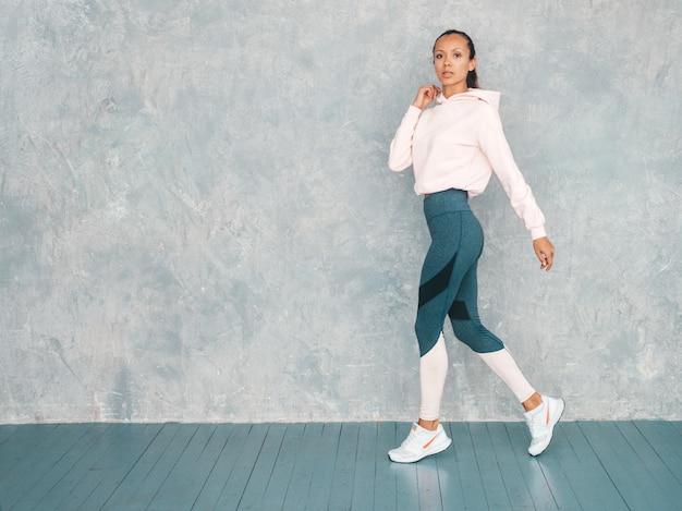 Schönes modell mit perfektem gebräuntem körper frau, die im studio nahe grauer wand aufwirft