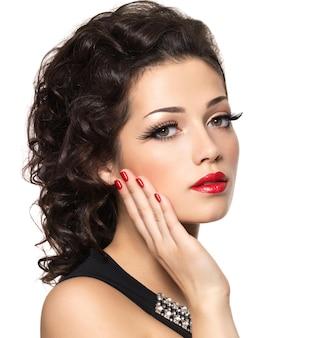 Schönes modell mit roter maniküre und lippen - lokalisiert auf weißer wand