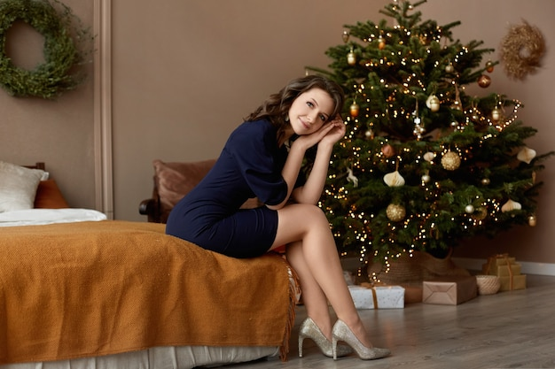 Schönes modellmädchen in einem eleganten kleid und hellen schuhen sitzt auf dem bett im innenraum, der für weihnachten dekoriert wird.