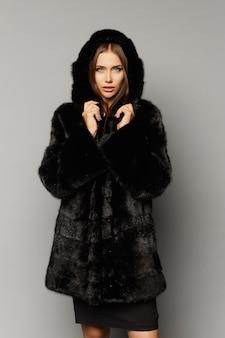 Schönes modellmädchen mit trendigem make-up im rock und schwarzem pelzmantel mit kapuze
