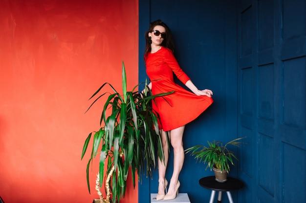 Schönes modemädchen mit dem langen haar, in der sonnenbrille und in rotem elegantem kleid, die auf wand des blauen rotes zwischen grünen bäumen aufwerfen.