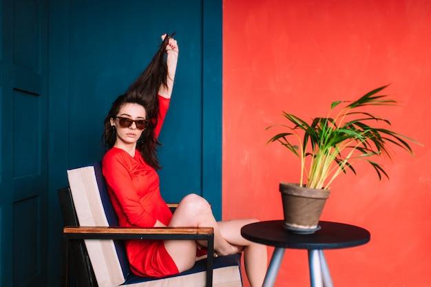 Schönes modemädchen mit dem langen haar, spanischem auftritt in der sonnenbrille und rotem elegantem kleid, das auf wand des blauen rotes im studio aufwirft.