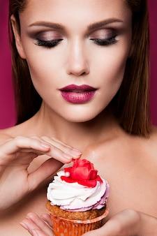 Schönes modemädchen mit kleinem kuchen