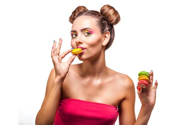 Schönes modemodellmädchen mit plätzchenfarben auf weißen oberflächenbonbons, schönheit, diät