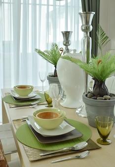 Schönes modernes keramisches geschirr in der grünen farbschemaeinstellung auf speisetische