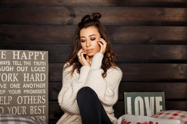 Schönes modisches frauenmodell in einem stilvollen strickpullover sitzt nahe einer holzwand