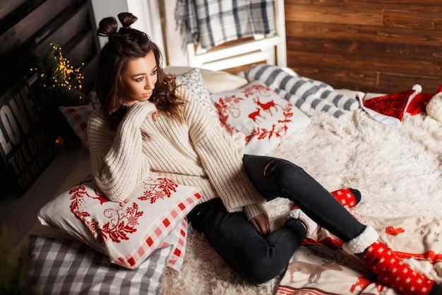 Schönes modisches junges mädchen mit einem haarschnitt in einem gestrickten weinlesepullover mit roten socken auf dem bett mit weihnachtsdekorationen