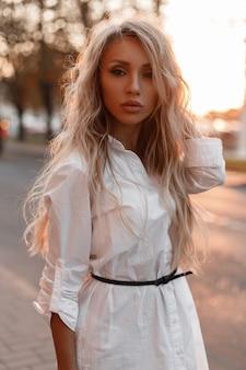 Schönes modisches junges mädchen mit frisur in stilvollen weißen kleidern wirft auf der straße bei sonnenuntergang auf