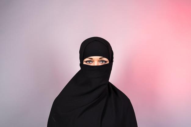 Schönes muslimisches mädchen, das schwarze burkanahaufnahme trägt.