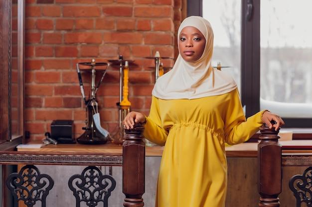 Schönes muslimisches mädchen im lächelnden hijab, das auf ihr essen in einem restaurant wartet.