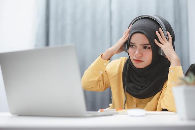 Schönes muslimisches studentenmädchen, das einen laptop verwendet, der online zu hause lernt. online-fernunterricht.