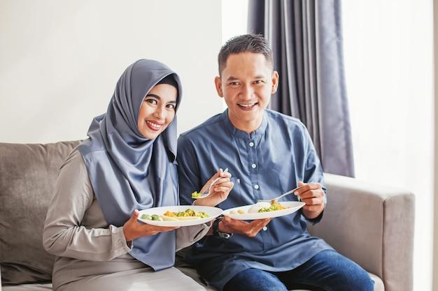 Schönes muslimisches südostasiatisches paar, das zusammen nasi campur isst