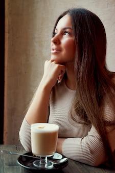 Schönes nachdenkliches glückliches mädchen, das im café sitzt
