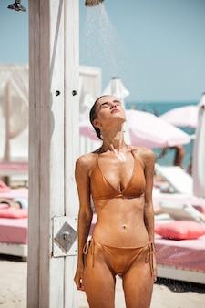 Schönes nachdenkliches mädchen im beige bikini, das verträumt ihre augen schließt, während es am strand duscht. porträt des jungen mädchens im badeanzug beim duschen beim verbringen der zeit am strand