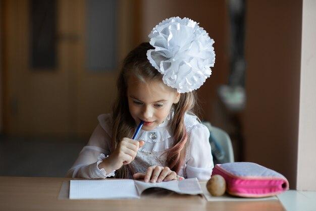 Schönes nachdenkliches mädchen in einem weißen hemd, das am tisch am fenster im klassenbummel zum schulkonzept sitzt