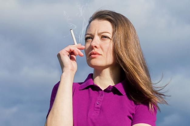 Schönes nachdenkliches mädchen mit zigarette