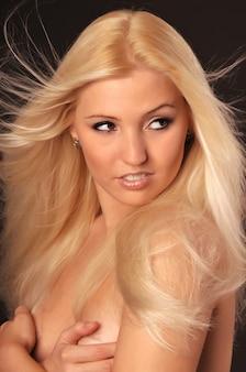 Schönes nacktes blondes kaukasisches weißes mädchen, das kamera betrachtet und brust mit den händen bedeckt.