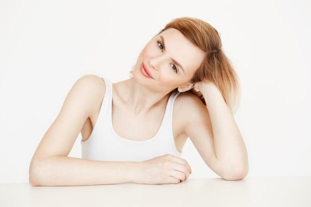Schönes natürliches blondes mädchen lächelnd am tisch sitzen. schönheits- und gesundheitskonzept.