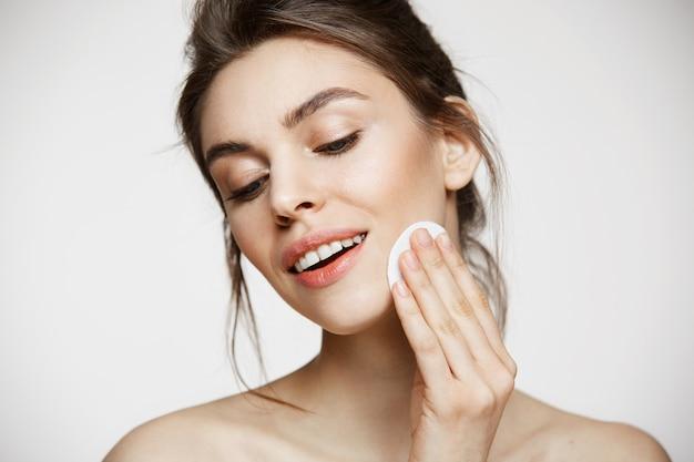 Schönes natürliches brünettes mädchen, das gesicht mit baumwollschwamm reinigt, der über weißem hintergrund lächelt. kosmetologie und spa.