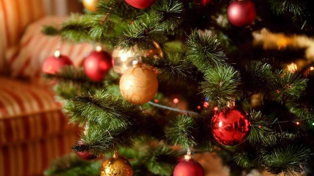 Schönes nebliges foto von bunten funkelnden kugeln und girlanden, die am neujahrsmorgen an weihnachten im wohnzimmer hängen. perfekter hintergrund für winterferien und feiern