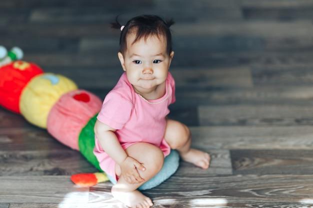 Schönes nettes baby kazakh ein jähriges mädchen, das zu hause auf boden sittimg ist