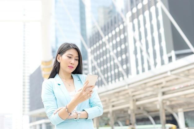 Schönes nettes mädchen in der geschäftsfrau kleidet unter verwendung des intelligenten telefoncomputergeschäfts concep