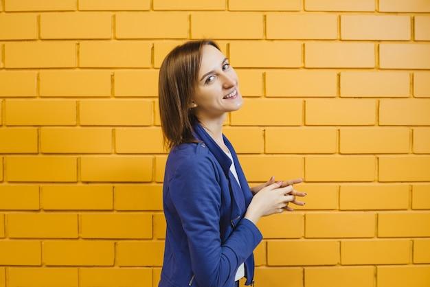 Schönes nettes modernes blondes mädchen in einer geschäftshaltung gegen eine gelbe backsteinmauer.