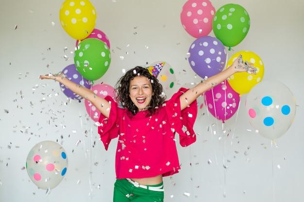Schönes nettes nettes mädchen mit farbigen ballonen. urlaub alles gute zum geburtstag.