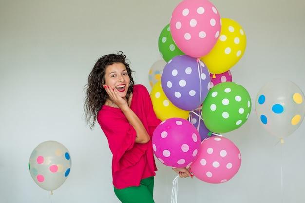 Schönes nettes nettes mädchen mit farbigen ballonen