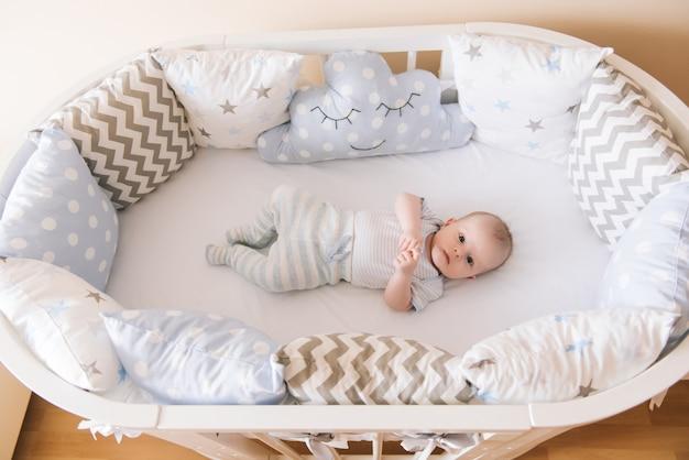 Schönes neugeborenes baby, das in einem ovalen bett liegt
