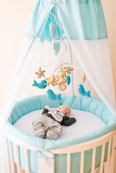 Schönes neugeborenes baby, das in einem ovalen bett mit schönen stoßstangen in zarten grau-, blau-, weißtönen liegt