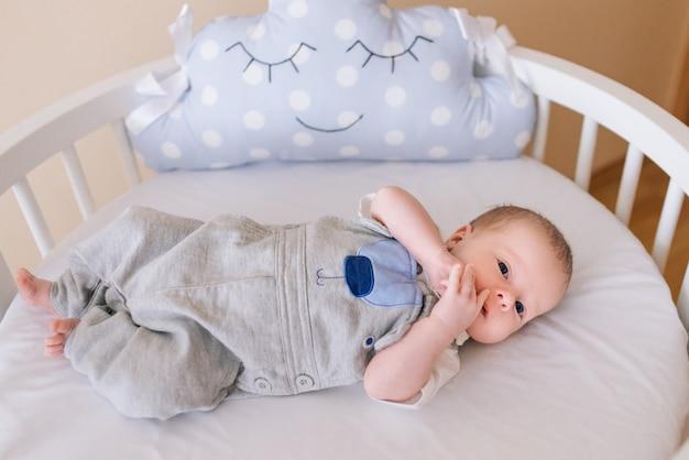 Schönes neugeborenes baby, das in einem runden bett mit schönen stoßstangen in zarten grau-, blau-, weißtönen liegt