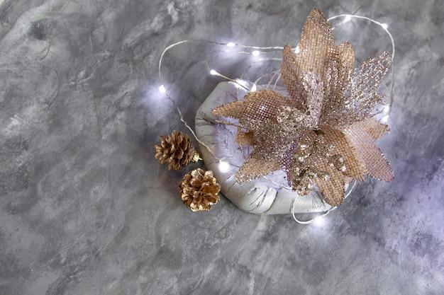 Schönes neujahrsdekor in silbergoldtönen eine ungewöhnliche blume tannenzapfen in einer betonschale stil...