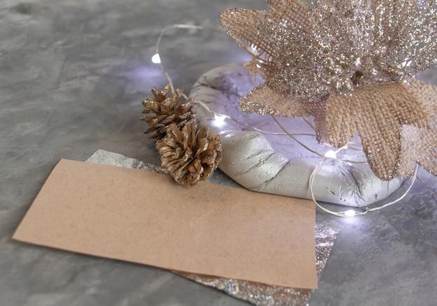 Schönes neujahrsdekor in silbergoldtönen ungewöhnliche blume tannenzapfen leere karte stilvoll und modern