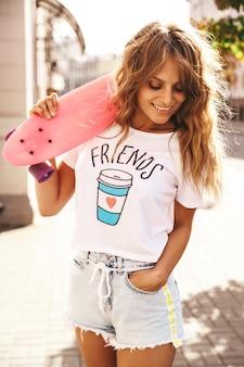 Schönes niedliches blondes teenager-modell ohne make-up in weißen hipster-kleidern des sommers mit rosa penny-skateboard, das auf dem straßenhintergrund aufwirft